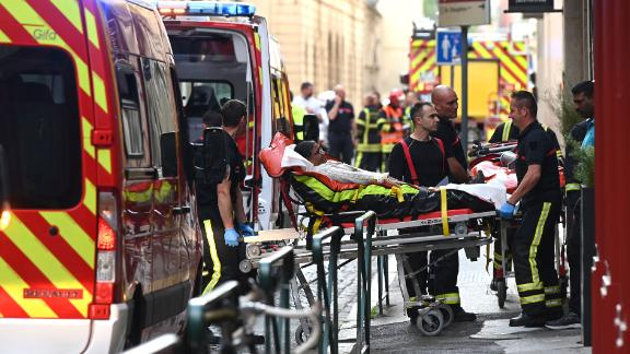 Emergency workers wheel a woman on a stretcher to a waiting ambulance in Lyon on Friday.