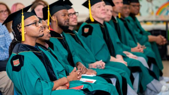 Larry Marshall (left) and fellow graduates sit at their commencement. They received Associate of Arts degrees from Washington University in St. Louis through the school