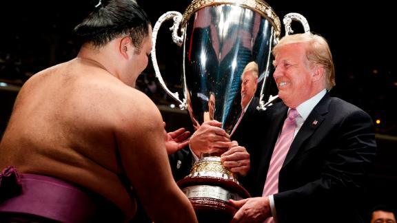 Donald Trump presents the President's Cup to the Tokyo Grand Sumo Tournament winner Asanoyama, at Ryogoku Kokugikan Stadium.