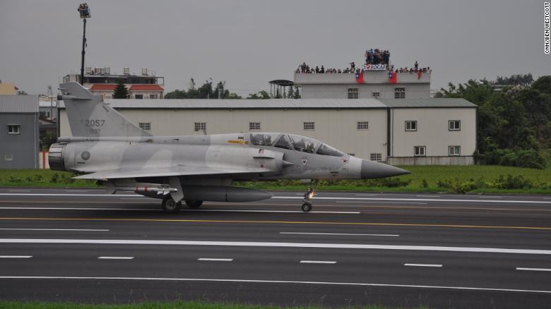 A Taiwan Mirage 2000 jet prepares to take off on a highway, during an exercise outside Taichung on Tuesday. In the background, onlookers wave the Taiwan flag.