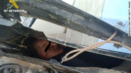An African migrant squeezed inside a compartment built behind a car dashboard.