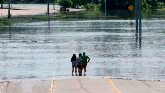 People peer out over the flooded Massard Creek from the middle of a road in Fort Smith, Arkansas.