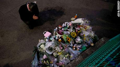 A man pays respects at a makeshift memorial for the victims of a knife attack Tuesday, May 28, 2019, in Kawasaki, just outside Tokyo. A man carrying a knife in each hand has attacked a group of schoolgirls waiting at a bus stop. (AP Photo/Jae C. Hong)