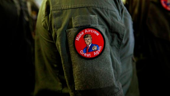 """A service member wears a patch that says """"Make Aircrew Great Again"""" while listening to President Donald Trump speak to service members aboard the USS Wasp on May 28."""