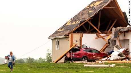 A woman walks away from a damaged house after several tornadoes reportedly touched down, in Linwood, Kansas, on May 29, 2019.