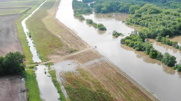 Water overtops a levee in Logan County, Arkansas, near state Highway 309, drone footage shows.