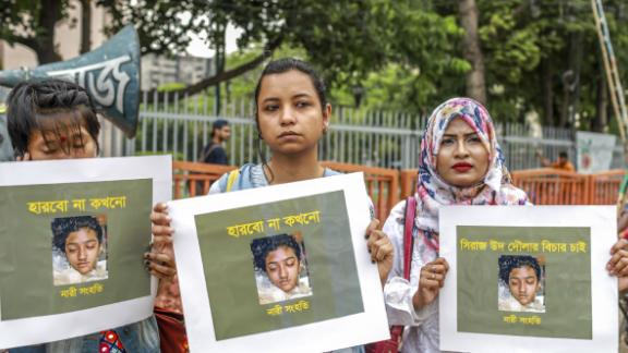 Bangladeshi women hold placards and photographs of schoolgirl Nusrat Jahan Rafi at a protest in Dhaka In this photo taken on April 12 following her murder.