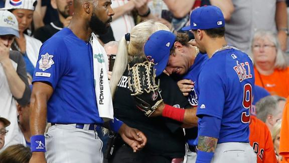 Cubs outfielder Albert Almora Jr., flanked by teammates Jason Heyward and Javier Baez, is comforted by a security guard after the child was struck during Wednesday night's game.