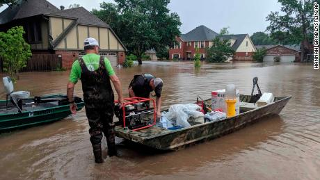 Father and son Brad and Bart Hindley take a boat to Brad's flooded house in Fort Smith, Arkansas, on  Wednesday, May 29, 2019.