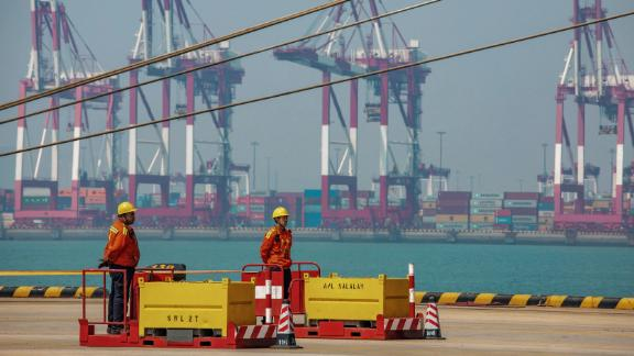 Two staff members stand at a port in Qingdao in China's eastern Shandong province on April 17, 2019. - China's economy beat forecasts as it remained steady with 6.4 percent growth in the first quarter amid tepid global demand, a US trade war and a debt battle, official data showed on April 17. (Photo by STR / AFP) / China OUT        (Photo credit should read STR/AFP/Getty Images)