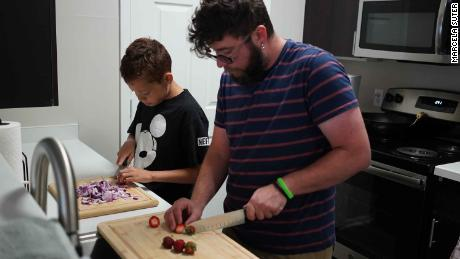 Damien, 13, cooks with his math teacher and foster parent, Finn Lanning, in Aurora, Colorado.