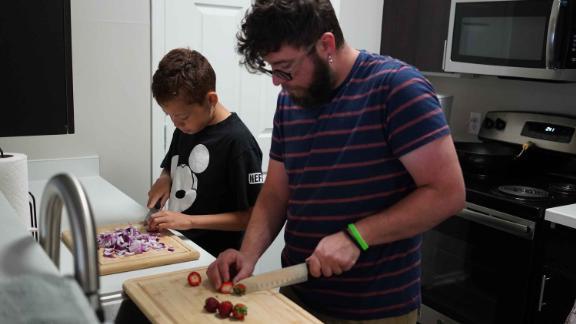 Damien, 13, cooks with his math teacher and foster parent, Finn Lanning, in Aurora, Colorado.
