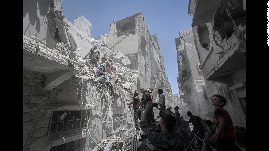 "Rescuers work at the scene of an airstrike in Idlib, Syria, on Monday, May 27. The fighting in Syria's last rebel-held province <a href=""https://www.cnn.com/2019/05/29/middleeast/idlib-bombing-slider-intl/index.html"" target=""_blank"">has left a trail of damage visible from space.</a>"