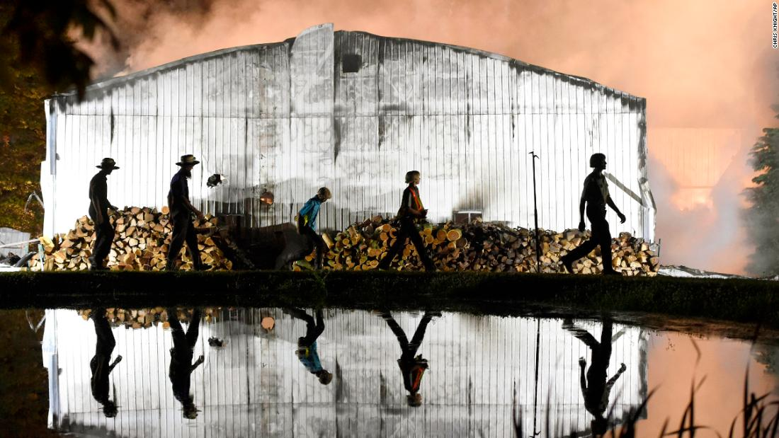 Amish farmers walk around the side of a building as firefighters battle a barn fire in Strasburg Township, Pennsylvania, on Wednesday, May 29.