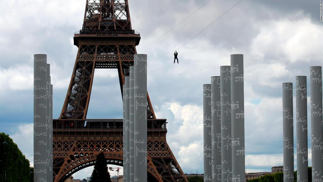 A person rides a zip line from the second floor of the Eiffel Tower in Paris on Tuesday, May 28.