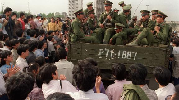 Pro-democracy demonstrators surround a truck filled of People's Liberation Army (PLO) soldiers on 20 May 1989 in Beijing on their way to Tiananmen Square.