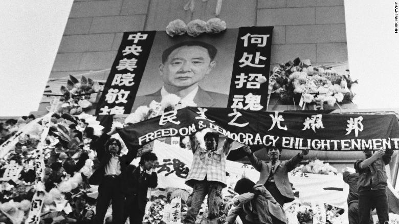 Chinese students hold aloft a banner calling for freedom, democracy and enlightenment on the Martyrs Monument in Beijing's Tiananmen Square, festooned with a giant portrait of Hu Yaobang, April 19, 1989.