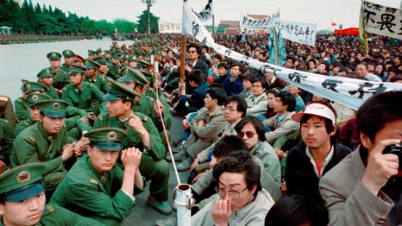 Some of the 200,000 pro-democracy student protesters sit face to face with policemen outside the Great Hall of the People in Tiananmen Square on April 22, 1989.