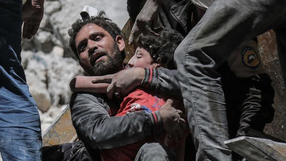 Nour Faham is carried from the rubble of a building destroyed during an airstrike in Ariha on May 27.