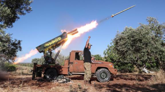 A Syrian fighter from the Turkish-backed National Liberation Front fires a heavy artillery gun from the jihadist-held Idlib province against regime positions in Hama province, on May 26.