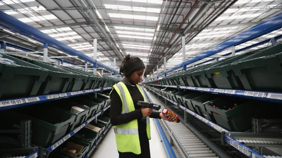 MILTON KEYNES, ENGLAND - JANUARY 03: A worker scans an item in the giant semi-automated distribution centre where the company