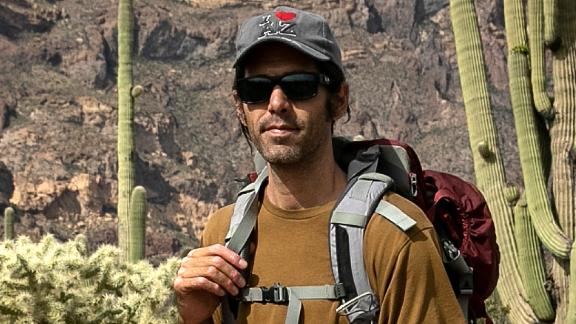 Scott Warren, a volunteer for the humanitarian aid organization No More Deaths, pauses while delivering food and water along remote desert trails used by undocumented immigrants on May 10 near Ajo, Arizona.