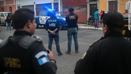 ICE agents with U.S. Homeland Security Investigations, and Guatemalan police stand at the scene of an early morning raid where a suspected human trafficker was taken into custody on May 29, 2019, in Guatemala City.