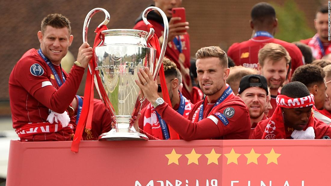 James Milner (L) and Jordan Henderson hold the European Champion Clubs' Cup trophy above an open-top bus at the start of the parade.