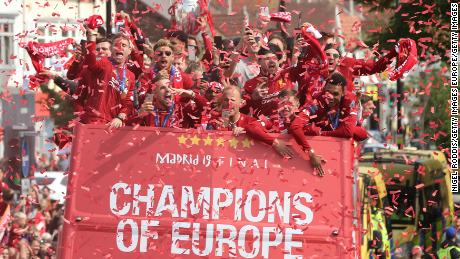 Liverpool players celebrate their Champions League victory surrounded by supporters in Liverpool.