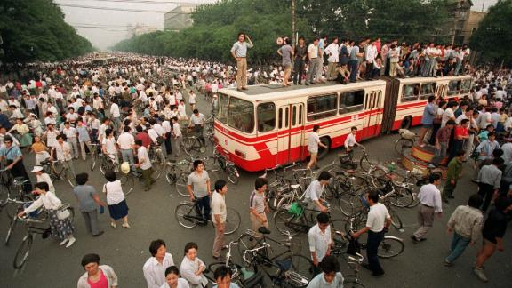 A crowd gathers at a Beijing intersection where residents used a bus as a roadblock to keep troops from advancing toward Tiananmen Square.