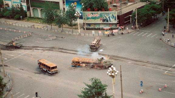 A Chinese army tank crashes through a barricade of burned buses in front of the Beijing Hotel on June 6, 1989.
