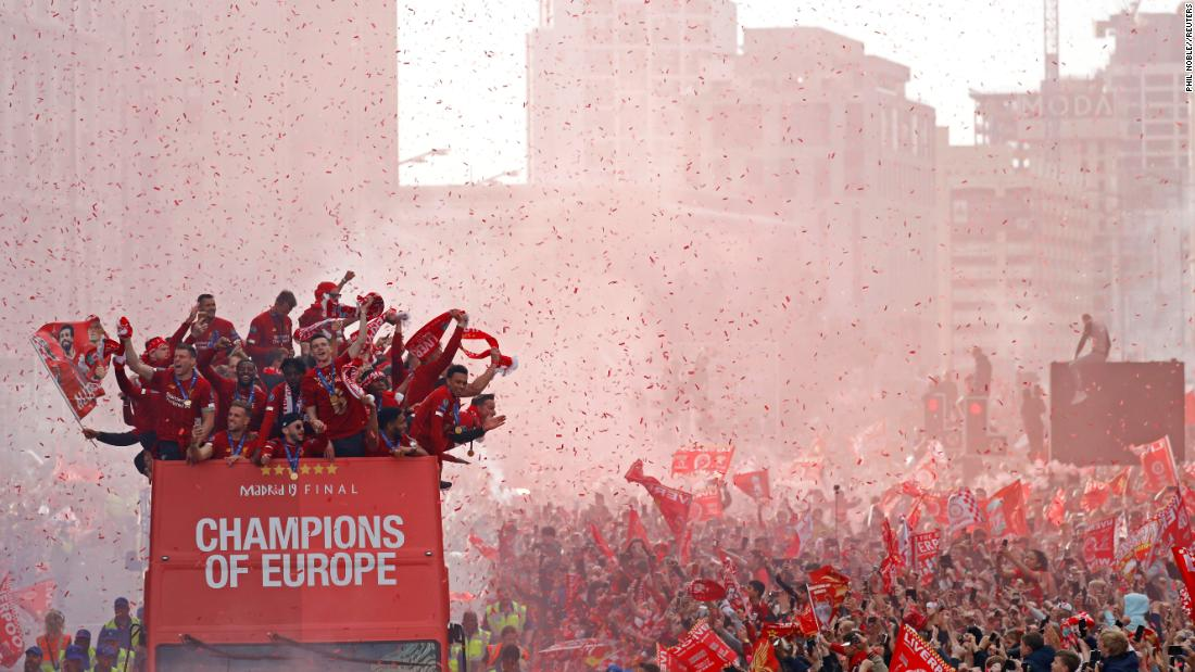 "Liverpool players celebrate on top of a team bus surrounded by cheering fans during a parade to celebrate their <a href=""https://www.cnn.com/2019/06/01/football/champions-league-final-result-liverpool-tottenham-spt-intl/index.html"" target=""_blank"">Champions League title</a> in Liverpool, England, on Sunday, June 2."