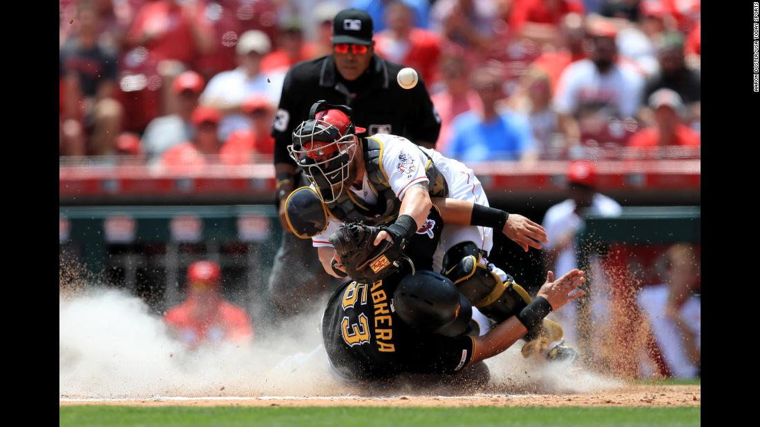 Pittsburgh Pirates right fielder Melky Cabrera collides at home plate with Cincinnati Reds catcher Tucker Barnhart to score a run during the fourth inning of their game at Great American Ballpark in Cincinnati on Monday, May 27.
