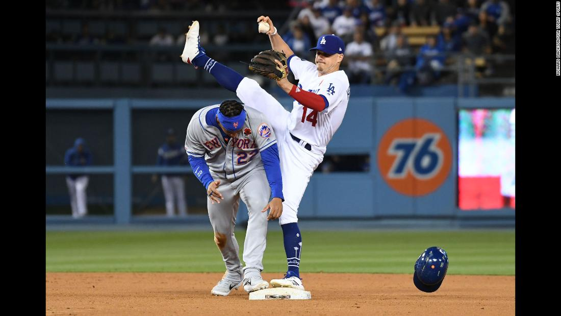 New York Mets first baseman Dominic Smith ducks under the leg of Los Angeles Dodgers center fielder Enrique Hernandez after being called out at second base during the eighth inning of their game at Dodger Stadium in Los Angeles on Monday, May 27.