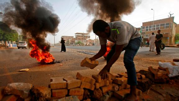 A Sudanese protester uses paving stones to block Street 60 as military forces tried to disperse a sit-in on June 3, 2019.