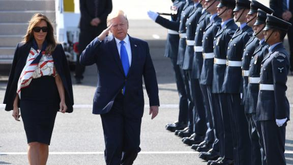The President salutes troops as he and the first lady arrive at Stansted Airport.