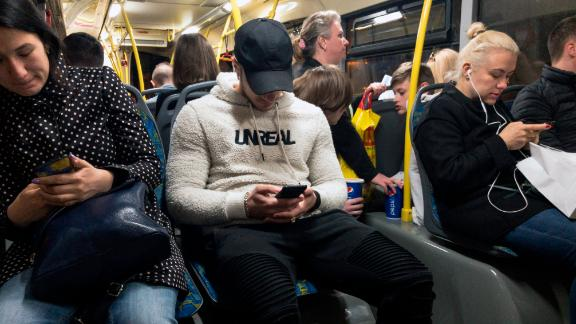 In this photo taken on Thursday, May 16, 2019, passengers look at their smartphones as they ride a bus in Moscow, Russia. Russia's communications regulator says that Tinder is now required to provide user data to Russian intelligence agencies. The Russian Communications Oversight Agency on Monday, June 3 published a new list of online services operating in Russia that are required to provide user data on demand to Russian authorities, including the FSB security agency. (AP Photo/Alexander Zemlianichenko)