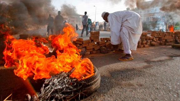 Protesters block a street with bricks and burning tires as military forces attempt to disperse a sit-in outside the army headquarters in Khartoum, Sudan, on Monday, June 3. More than 100 protesters were killed when the military opened fire to break up the sit-in, according to a local doctors' union.