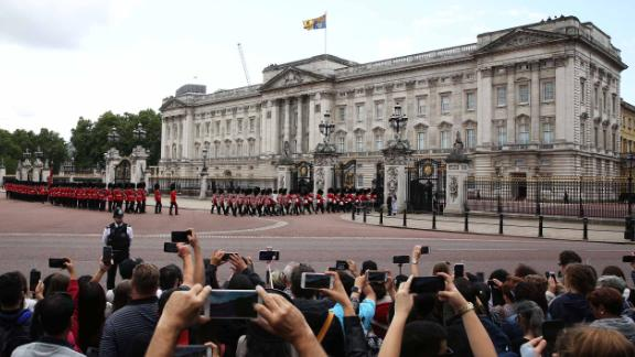 People outside Buckingham Palace photograph the Changing of the Guard ahead of Trump