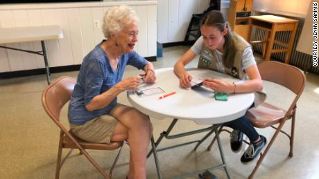 Nancy Taylor consults Girl Scout Cadette Sarah Middleton for advice with her smartphone.