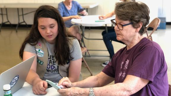 Girl Scout Cadette Maura Sammis (left) helps an attendee at a smartphone clinic for senior citizens.