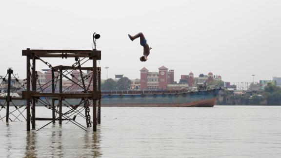 A boy jumps into the Ganges River to cool off on a hot summer day in Kolkata, India, on Monday, June 3.