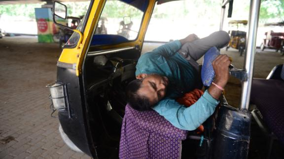 An Indian auto driver rests under a bridge on a hot summer afternoon in Allahabad on Sunday, June 2.