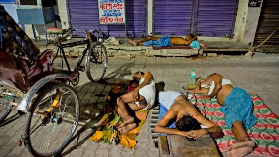 Indian laborers sleep on a side walk in Prayagraj on Sunday, June 2.
