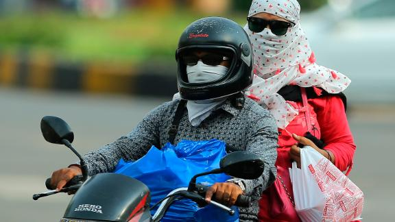 Commuters cover their faces with clothes to protect themselves from sun on a hot summer day in Hyderabad on Monday, June 3.