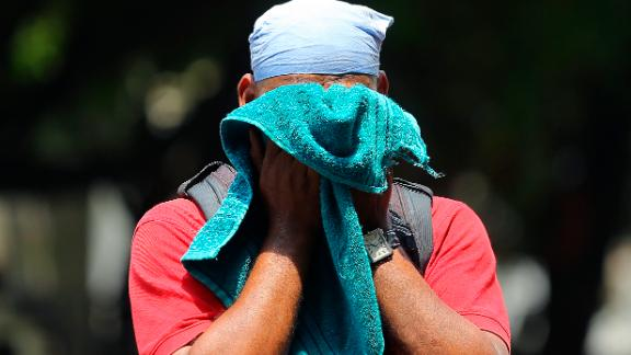 An Indian man uses a towel to wipe the sweat on his face on a hot and humid summer day in Hyderabad on Monday, June 3.