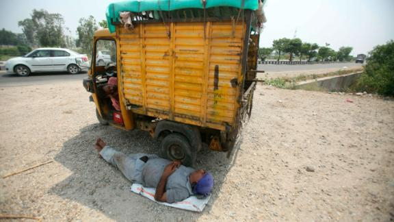 An Indian laborer takes a rest under the shade of an auto-rickshaw on a hot summer day in Jammu on Monday, June 3.