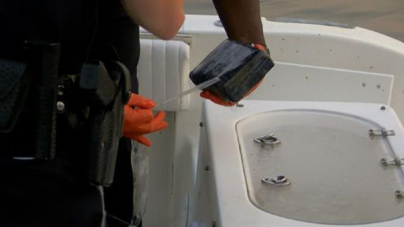 The North Charleston police examine a brick of the suspected cocaine found by the fishermen.