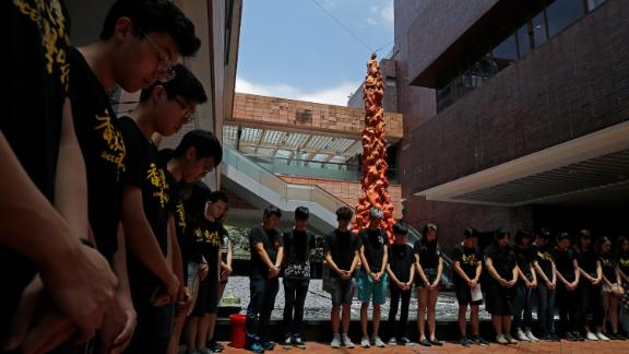"""Students at the University of Hong Kong observe a minute of silence in front of the """"Pillar of Shame"""" statue."""