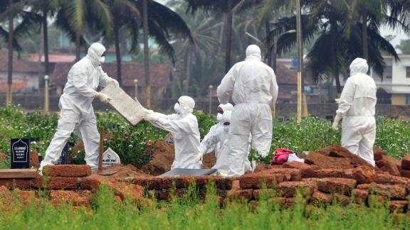 Doctors and relatives wearing protective gear dig a grave to bury the body of a Nipah virus victim on May 24, 2018.